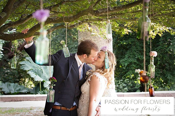 purple flowers in bottles hanging from trees wedding flowers passion for flowers