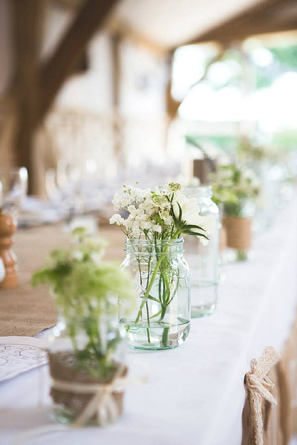 cripps barn wedding flowers top table with jam jars vases hessian