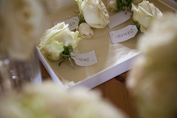 cream rose buttonholes wedding with name tags
