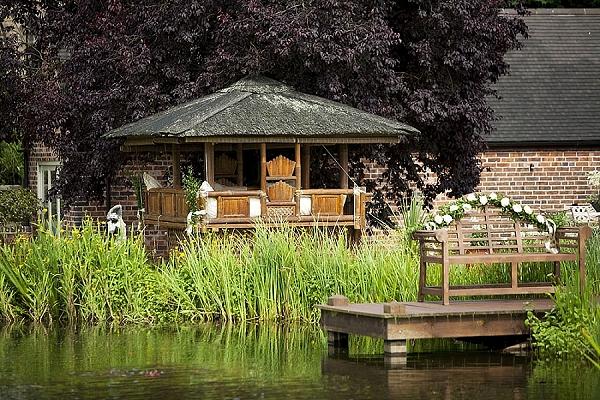 outdoor wedding flower garland over wooden bench