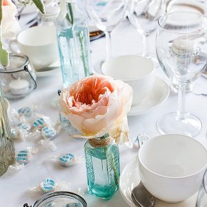 peach roses wedding flowers in mint green bottles centrepieces