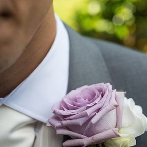 purple rose button holes white lisianthus groom