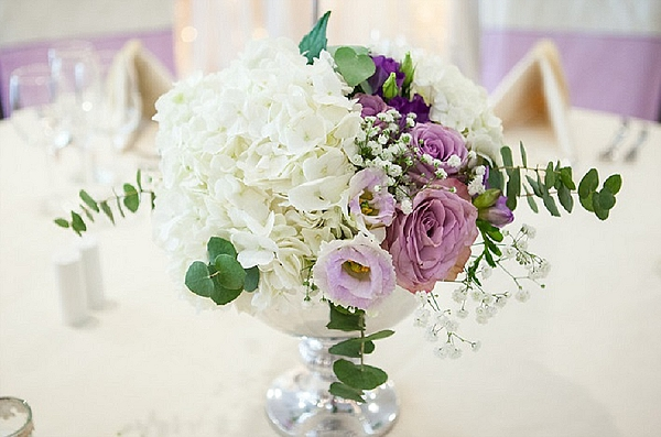 purple wedding flowers lilac centrepieces footed bowls white hydrangeas purple lisianthus roses  Mallory Court Passion  for Flowers Florists