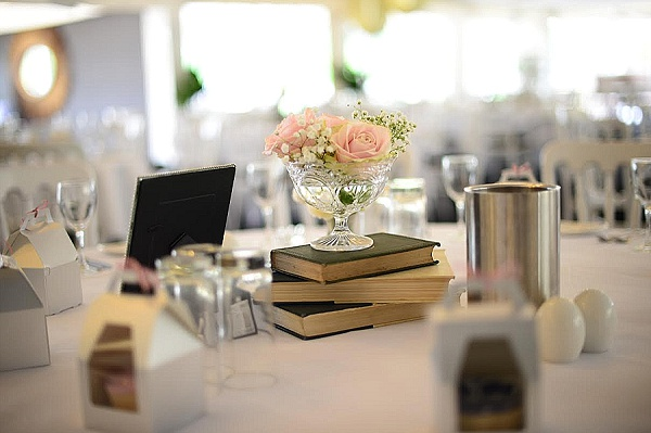centrepieces moxhull hall vintage pink roses in crystal vases on stack of books