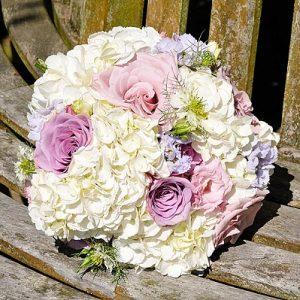 cream hydrangeas pink roses purple flowers wedding bouquets