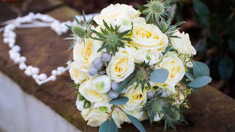 beautiful winter wedding bouquet cream and grey tones roses ranunculus thistles eucalyptus