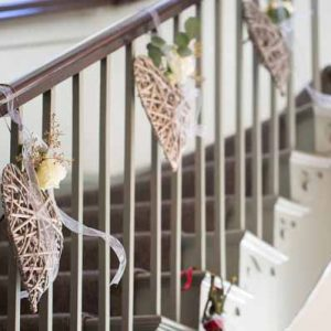 staircase decorated with wicker hearts and roses warwick house wedding