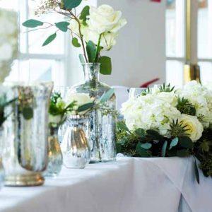 top table wedding flowers cream roses foliage and mercury silver vases warwickhouse winter wedding