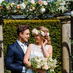 Stunning-flower-arch-for-outdoor-wedding-ceremony-at-Birtsmorton-Court-by-Passion-for-Flowers-bride-is-wearing-a-rose-flower-crown