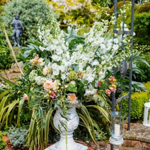 Wow-factor-urn-framing-entrance-to-outdoor-ceremony-peach-cream-green-florlas-Wedding-florist-Passio-for-Flowers