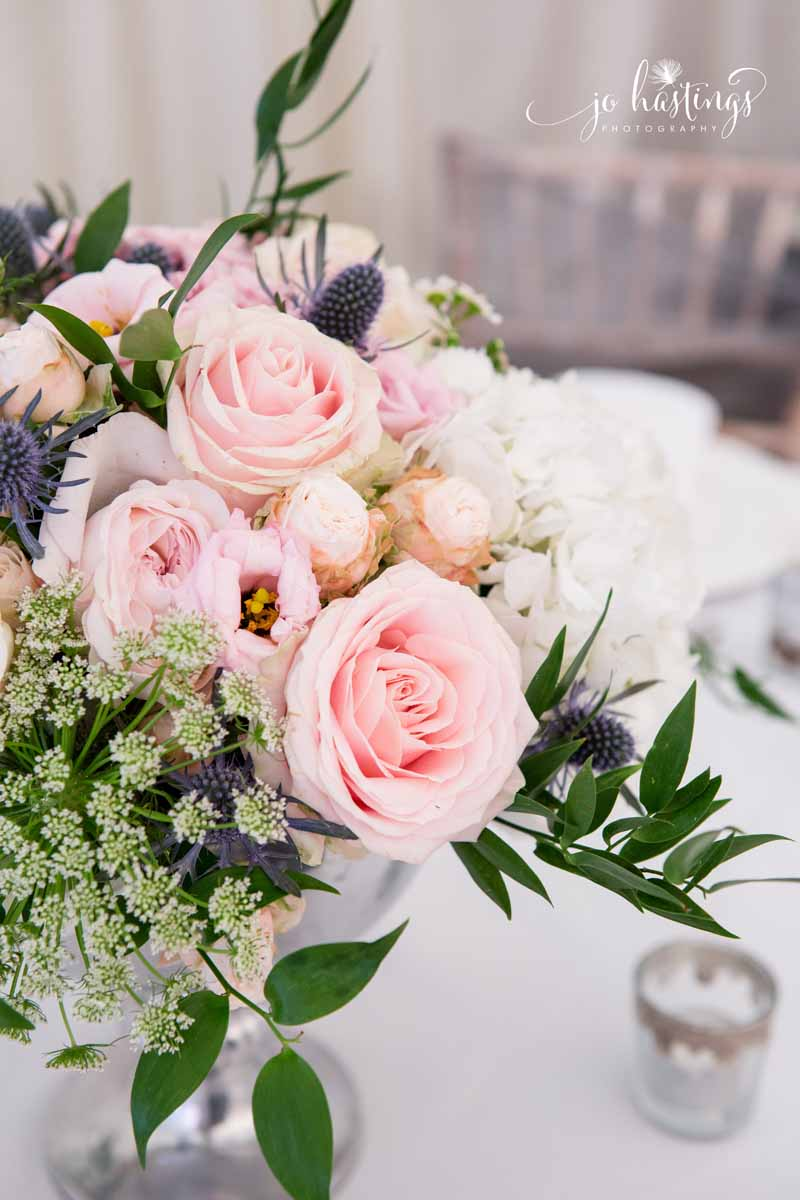 Blush pink roses and dusty blue thistles wedding centrepiece flowers low footed silver vases (1)
