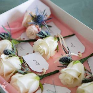 Cream rose button holes with dusty blue thistles by Passion for Flowers
