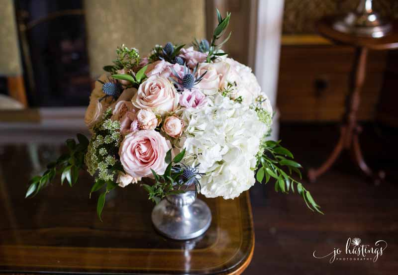 Dusty blue and pink flowers in silver footed bowl at wedding ceremony Heath House