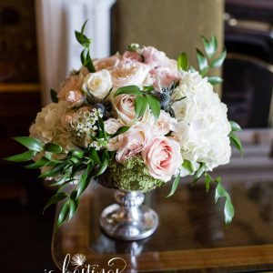 Footed silver bowl with dusky pink roses, dusty blue thistles and hydrangeas for ceremony floral arrangement at Heath House wedding