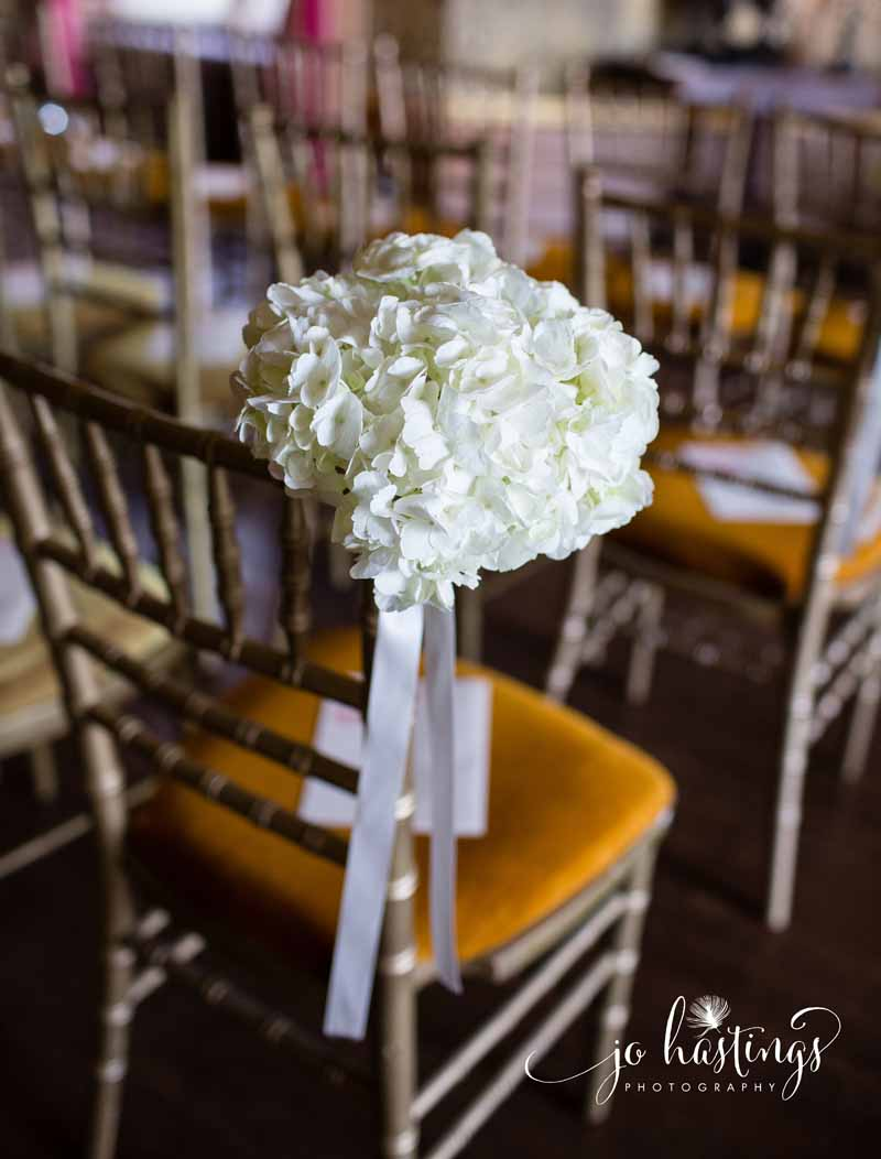 Hydrangeas tied to the aisle chairs for indoor wedding ceremeony at Heath House by Passion for Flowers