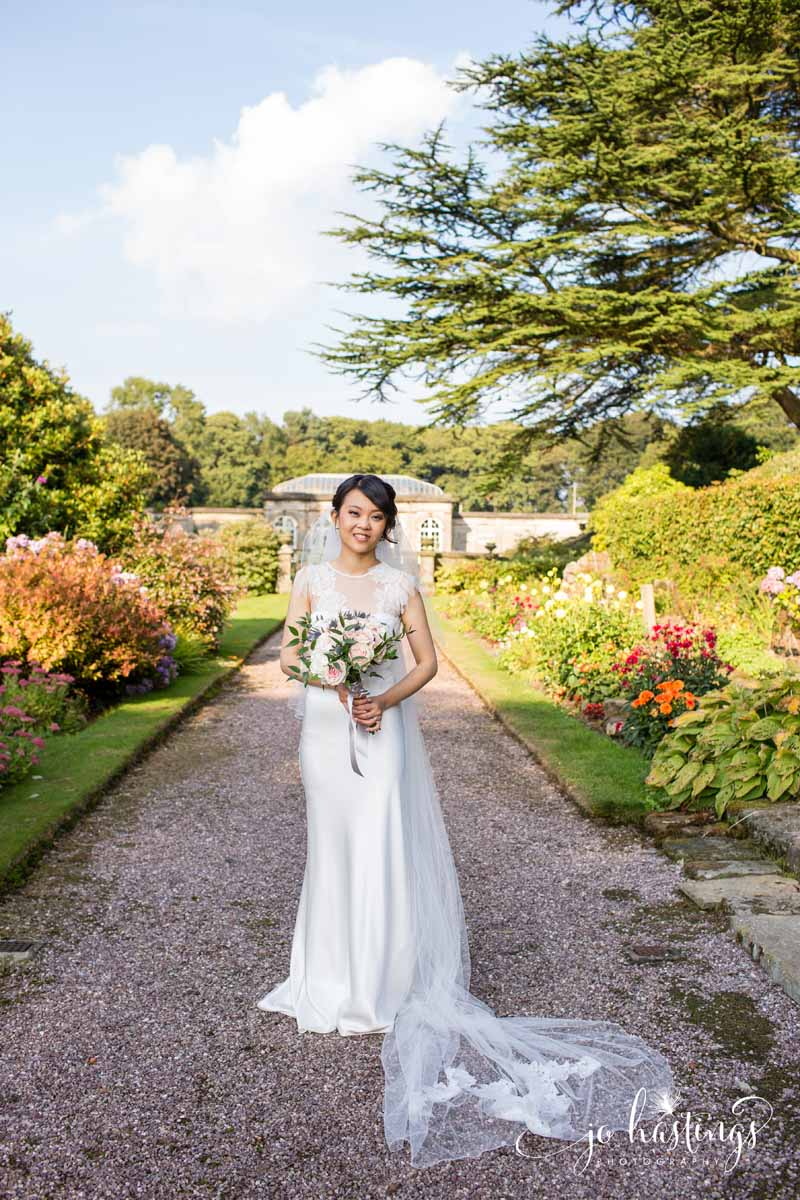 Wedding at Heath House bride in gardens with her bridal bouquet by Passion for Flowers