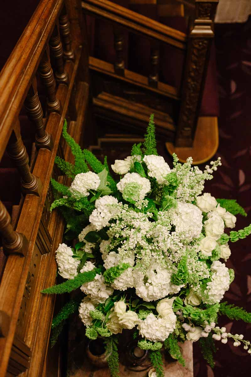 Green and white flowers in urns