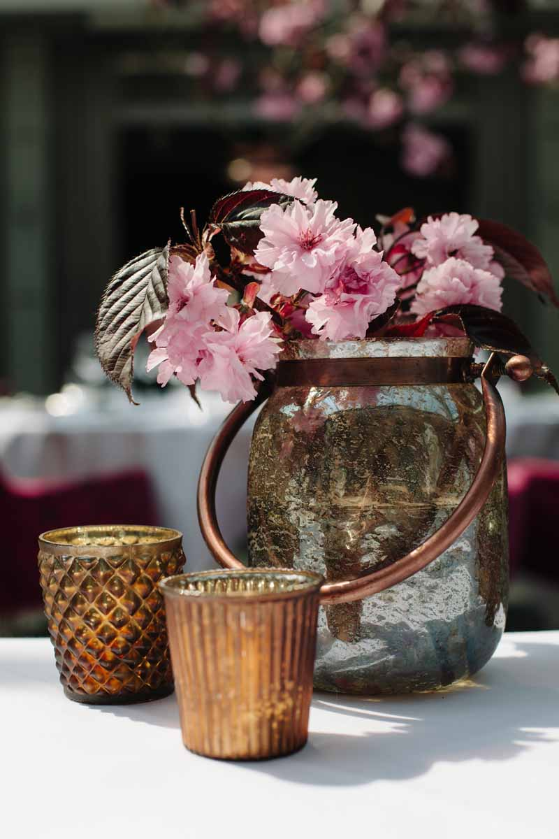 Bronze vases and votives with pink blossom perfect for a wedding centrepiece