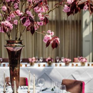 Tall centrepices bright pink blossom in bronze vases at Hampton Manor - flowers by Passion for Flowers @kmorganflowers