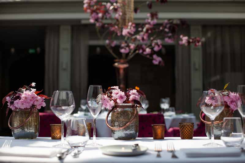 Top table wedding flowers bright pink blossom in bronze low vases and votives at Hampton Manor by Passion for Flowers @kmorganflowers