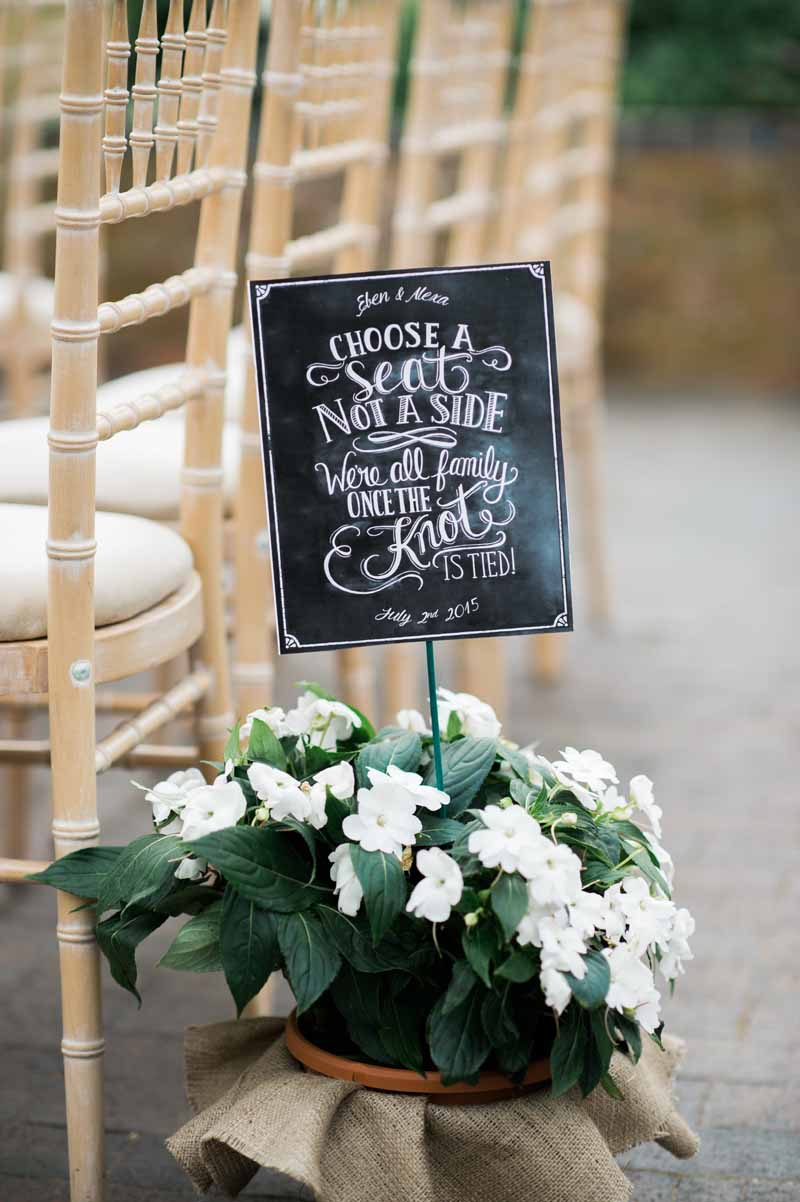 Chalkboard choose a seat not a side ceremony sign at Wethele Manor