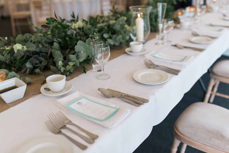 Top table eucalyptus garlands and hurricane lamps for marquee wedding