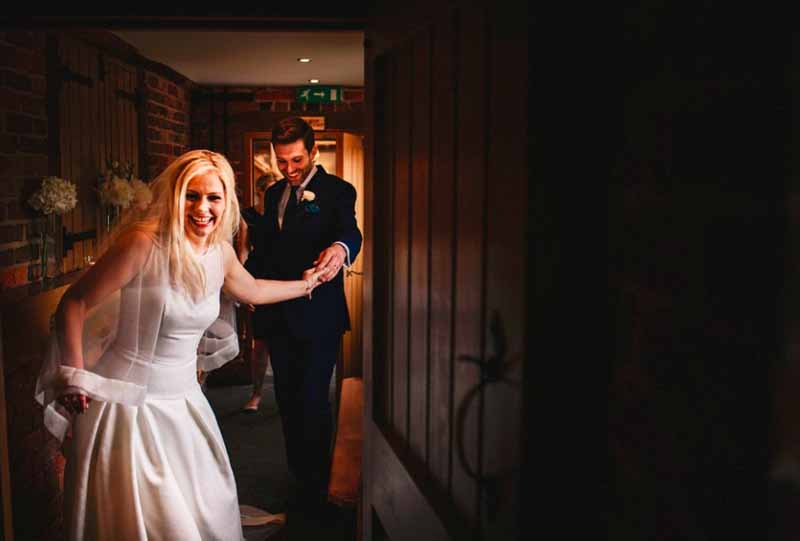 bride and grooom walking through curradine-barns-hydrangeas-to decorate the sideboards