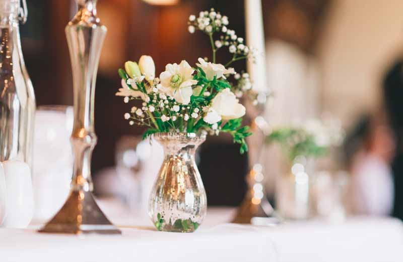 Small mercury silver vases with delicate flowers for top table Ettington Park Wedding Flowers
