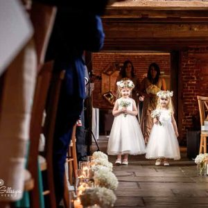 Aisle decorations using hydrangeas with cute flower girls and their flower crowns by @kmorganflowers