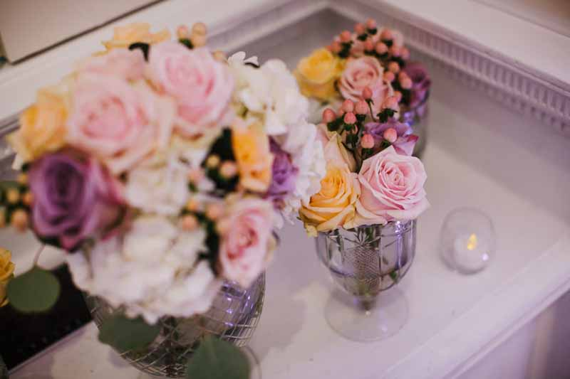 glass-footed-bowls-of-pink-purple-peach-roses-for-wedding-centrepieces-compton-verney-1