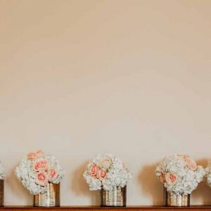 luxe-gold-vases-wedding-centrepieces-of-white-hydrangeas-peach-roses-gold-and-peach-wedding