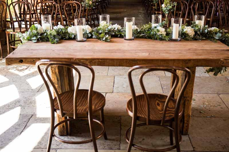 wedding-ceremony-table-foliage-eucalyptus-runner-with-glass-candles-lanterns