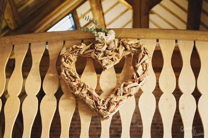 Wooden-heart-decorated-with-flowers-on-balcony-at-Shustoke-Farm-Barns