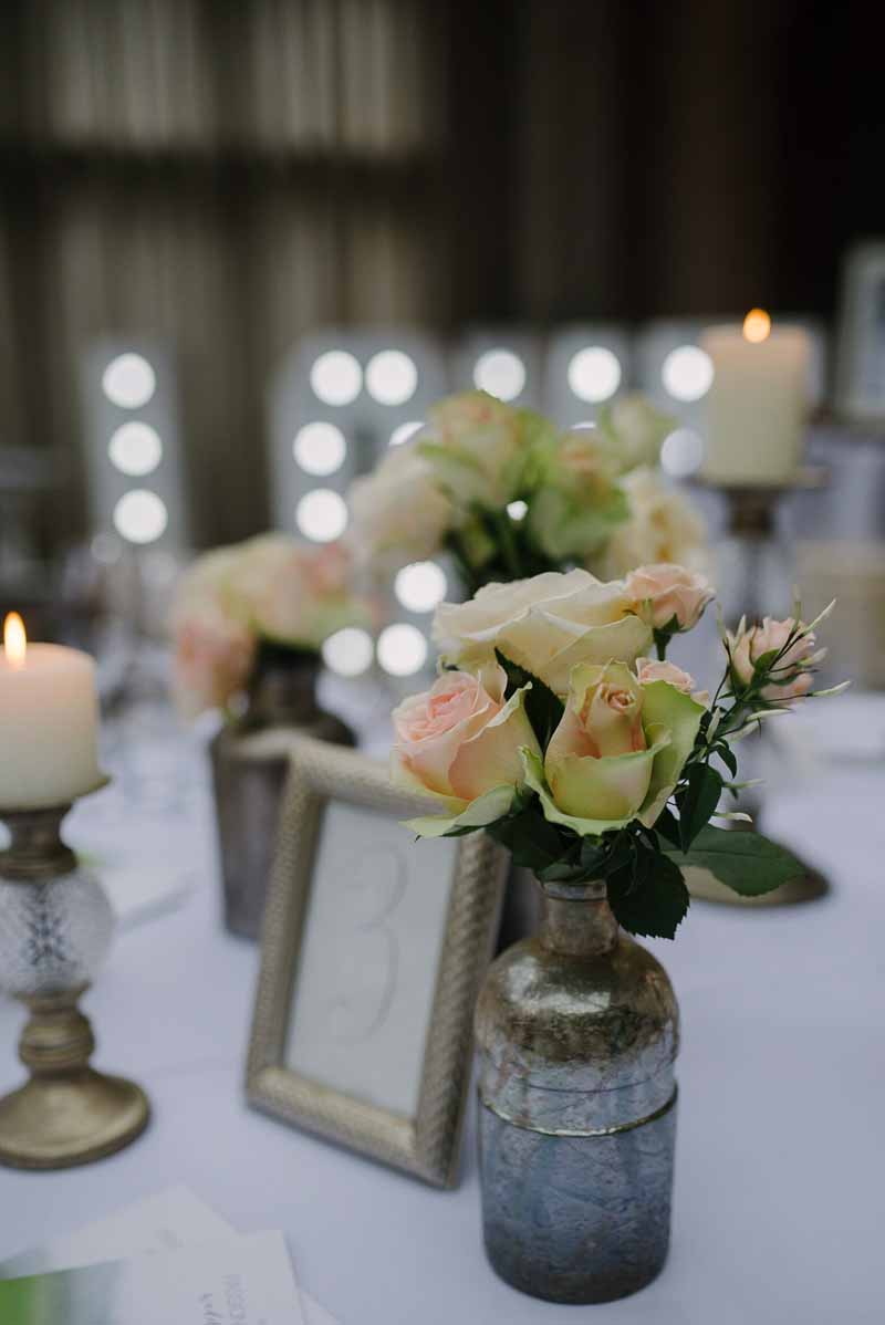 Bronze bottles with peach pink roses wedding flowers at Hampton Manor – Passion for Flowers (1)