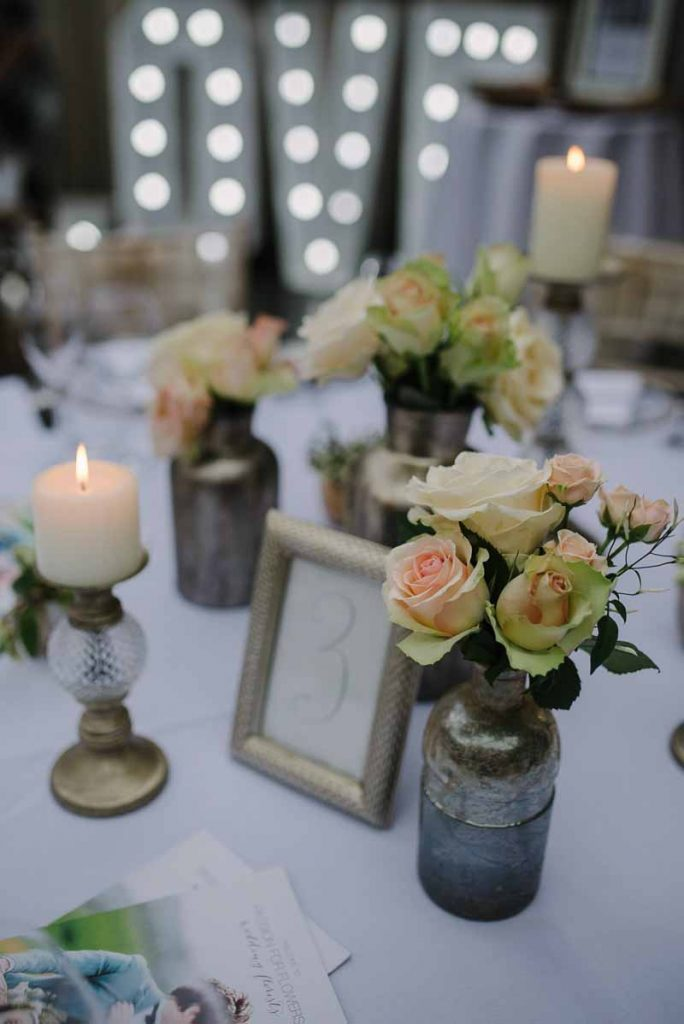 Bronze bottles with peach pink roses wedding flowers at Hampton Manor - Passion for Flowers