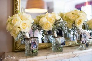 Cream rose bouquets with dusty miller in crystal vases with bridesmaids photos
