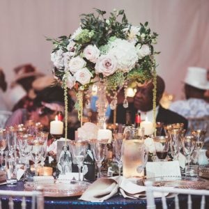Elegant tall wedding centrepiece crystal candle stick nude pink white green flowers trailing with candles and navy sequin table cloth Iscoyd Park