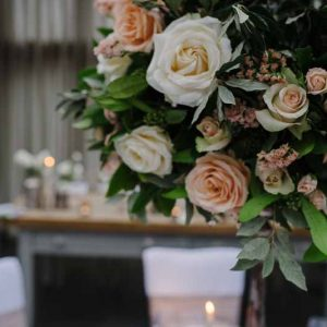 Peach cream roses with foliage wedding centrepieces