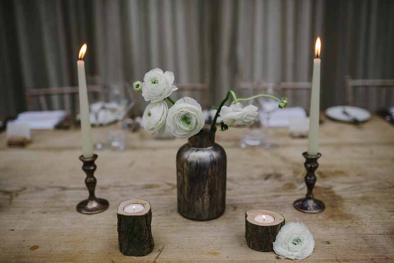 Wooden top table simple display of bronze bottles with white ranunculs for spring wedding