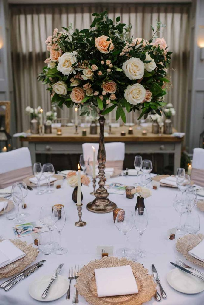 Tall bronze centrepieces wedding flowers at Hampton Manor by Passion for Flowers - peach cream foliage (1)