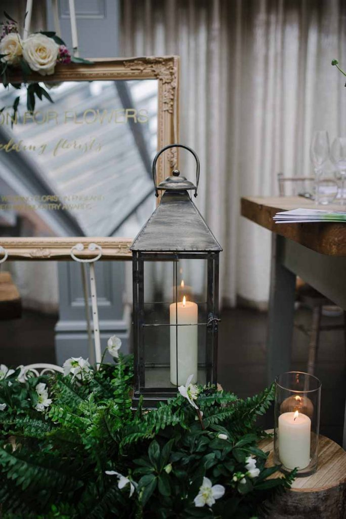 Woodland wedding decor ferns tree stumps bronze lanterns all available to hire from Passion for Flowers - Hampton Manor wedding fair (1)