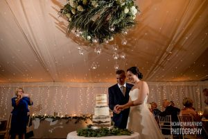 Amazing wedding cake flowers foliage around cake with hanging ring and candles above
