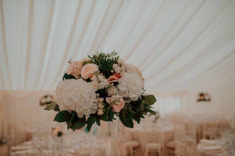 tall centrepieces marquee in glass vases Priory Farm