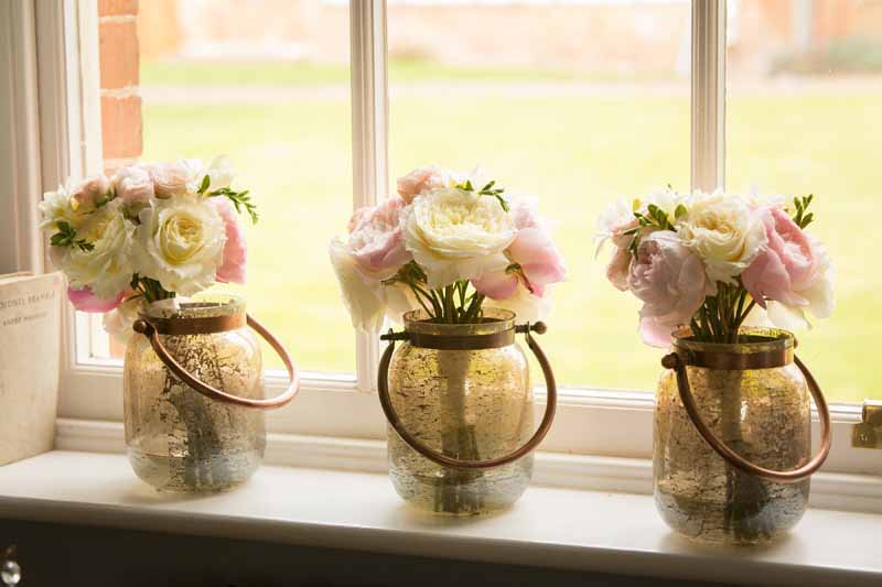Bridesmaids bouquets in bronze vases