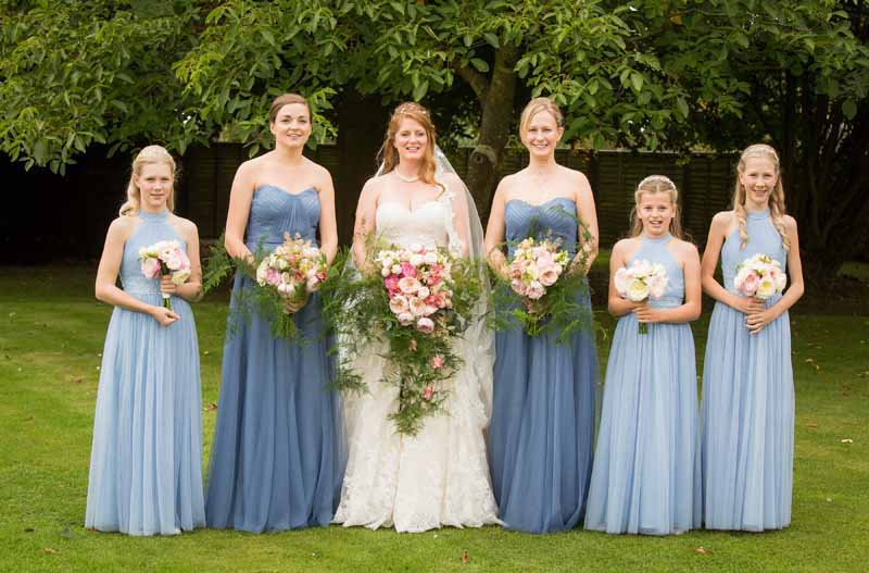 Large trailing pink bouquets with blue bridesmaids dresses