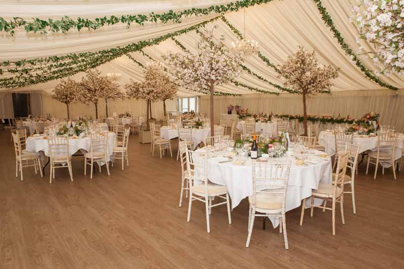 Stanbrook Abbey marquee wedding centrepieces ivy from celiing tree in marquee
