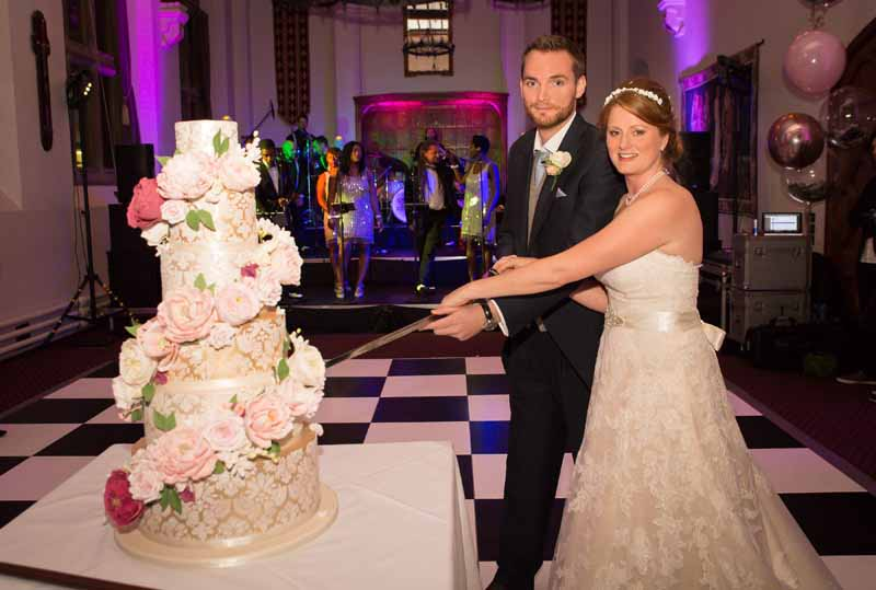 Wedding cake cutting with sword Stanbrook Abbey