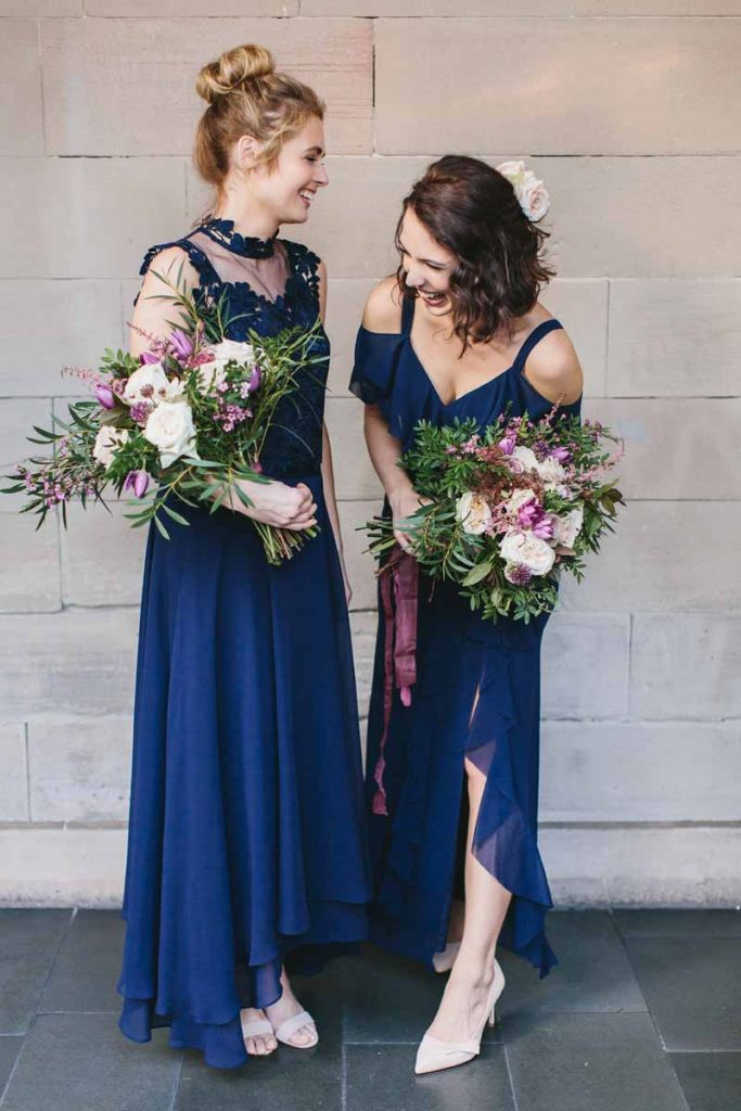 Deep pink and green bridesmaids bouquets with navy blue dresses