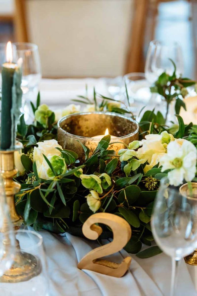 Gold-and-green-wedding-centrepieces-low-gold-lanterns-candlesticks-table-numbers-green-foliage-and-flowers