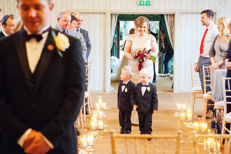 Page boys walking down aisle lit by lanterns Hampton Manor